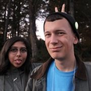 Girl Makes Funny Face Behind Teen Boy Wearing A Hat